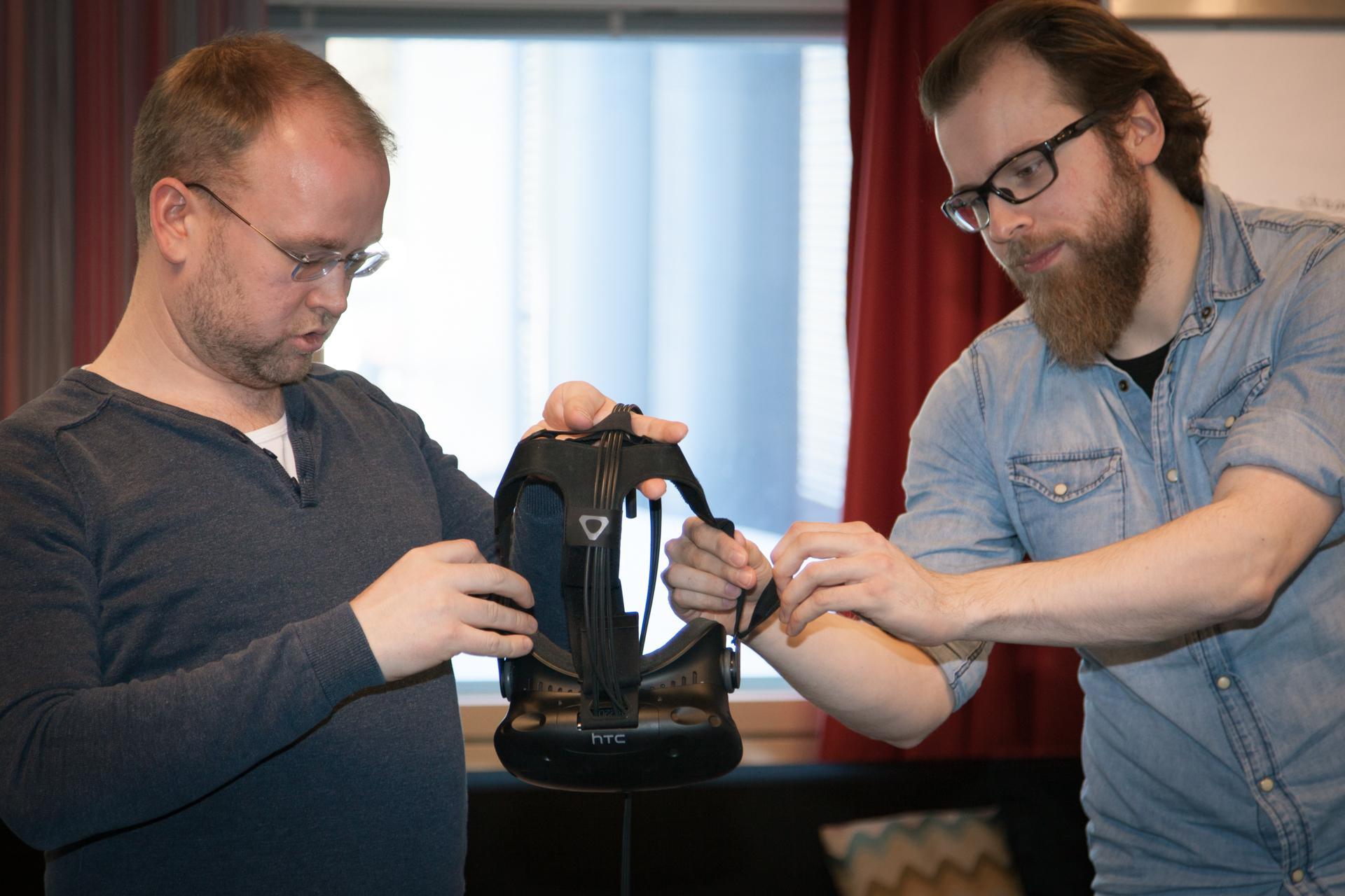 Äkräs-hankepäivän aikana testattiin virtuaalista puunkaatoa. Ohjelmoija Mikko Pallas (oik.) Lapin AMK:sta auttaa 4H-liiton metsäasiantuntija Sampo Juhajokea virtuaalilasien kanssa.