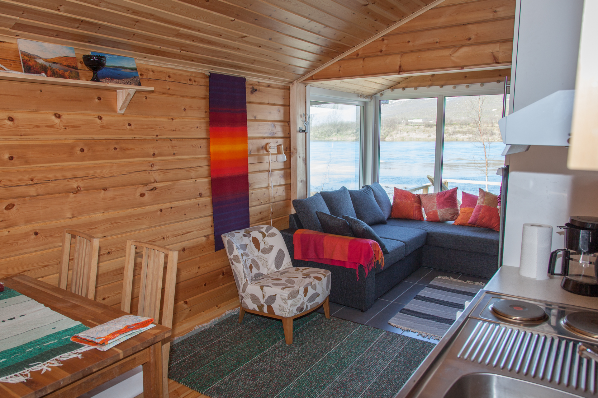 Aurora on yksi Alma Arktikan vuokramökeistä. Virtaavaa Tenojokea voi katsella sohvalta tai terassin kylpypaljusta.