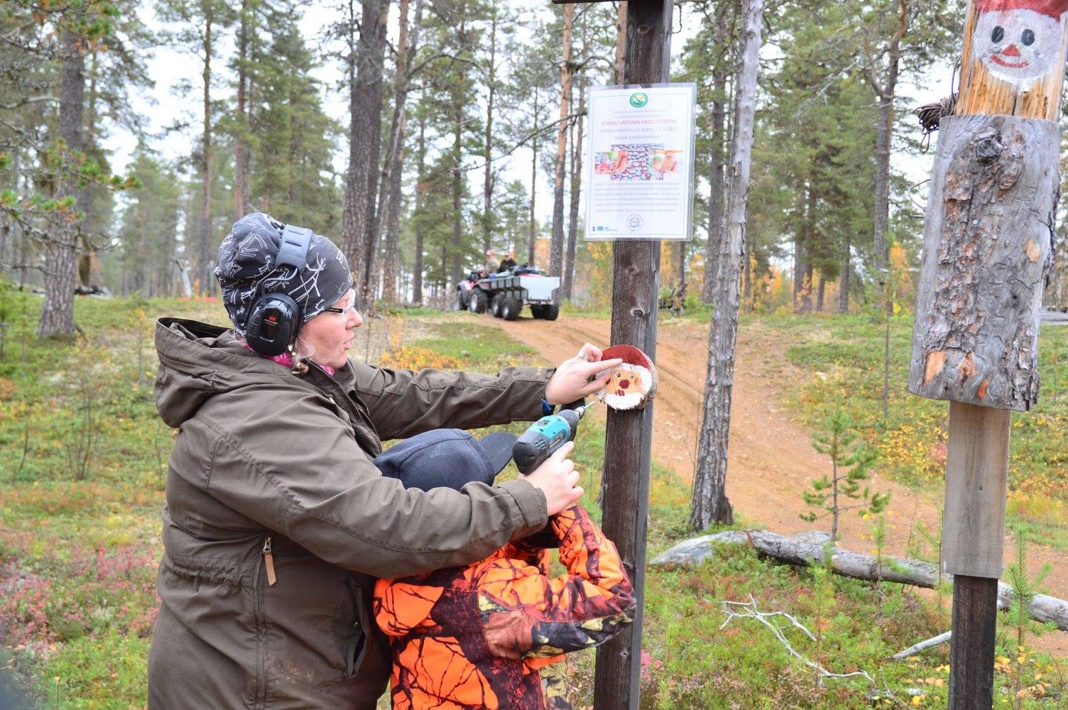 Reija Aaltonen avustaa poikaansa Akseli Pulskaa alulle aivan ensimmäisen kiekon ripustuksessa.
