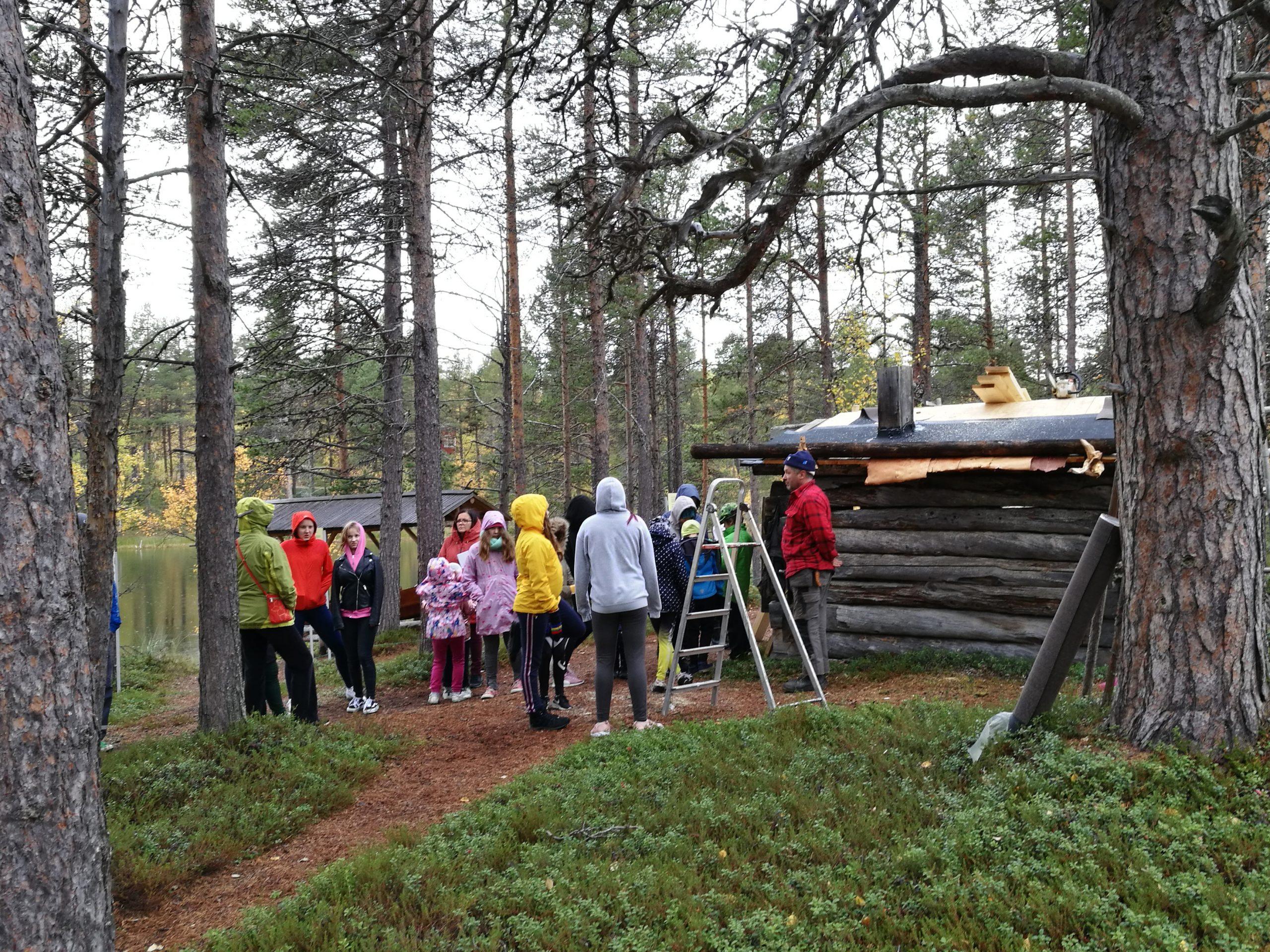 Lapsia tutustumassa turvekaton tekemiseen, metsämaisemassa, keskellä vanha puura.