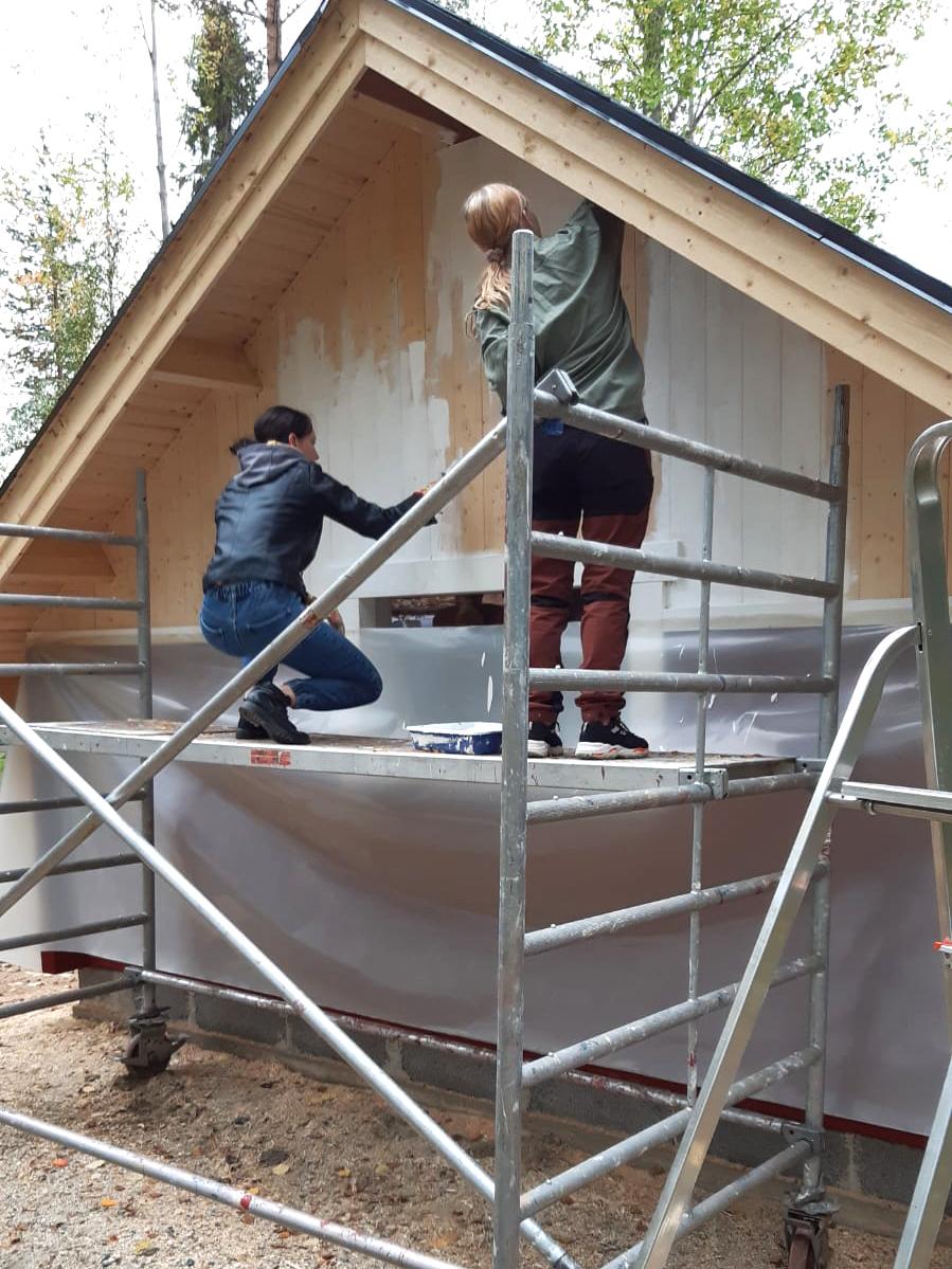 Nuoret rakennustelineellä maalaamassa kotaa.
