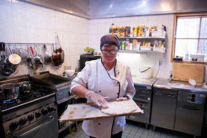 Keittiö, nainen tarjoilee ohraleipää.