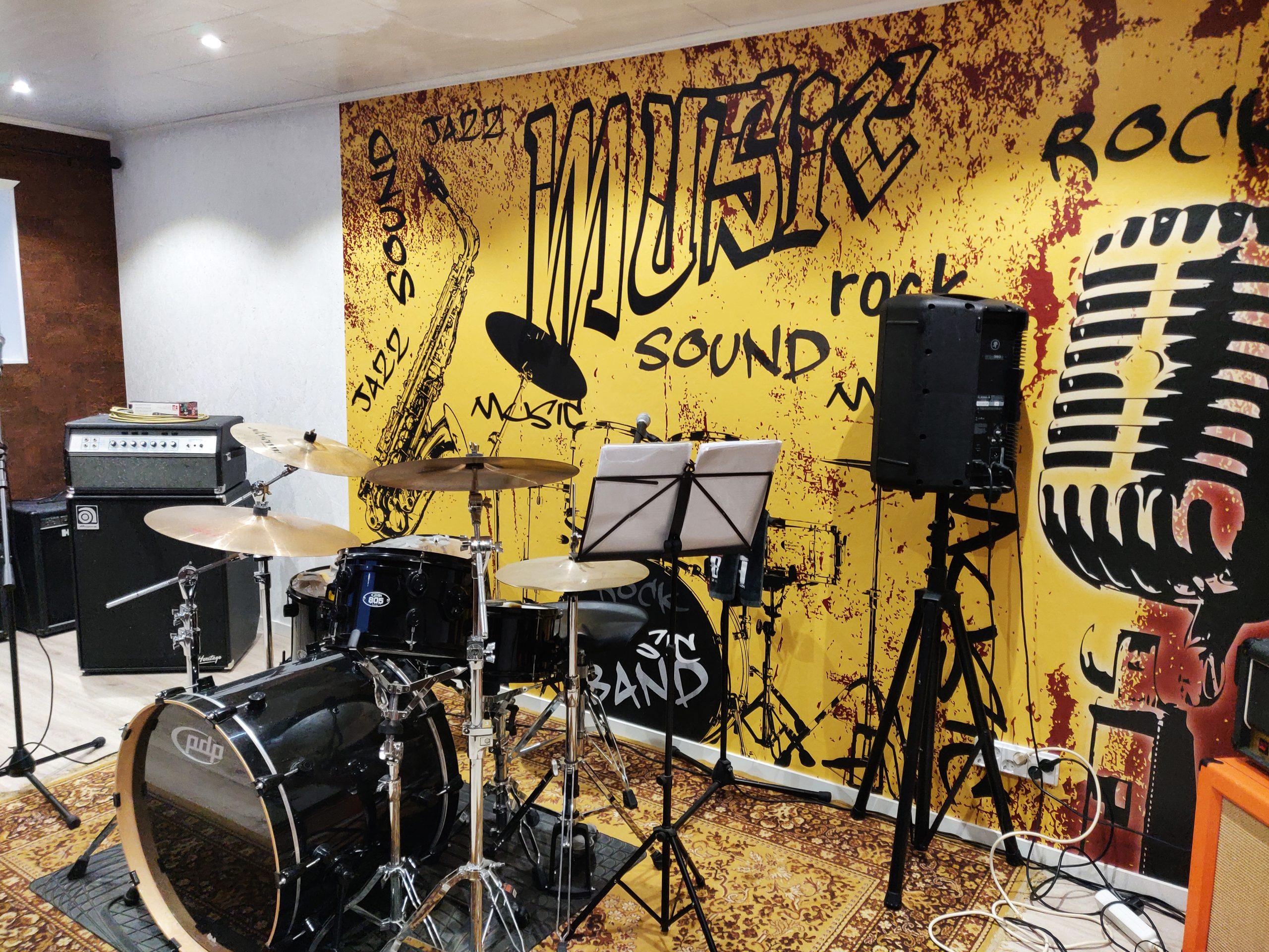 Musiikin harrastetila, rummut, monitoreja, värikäs taustatapetti.