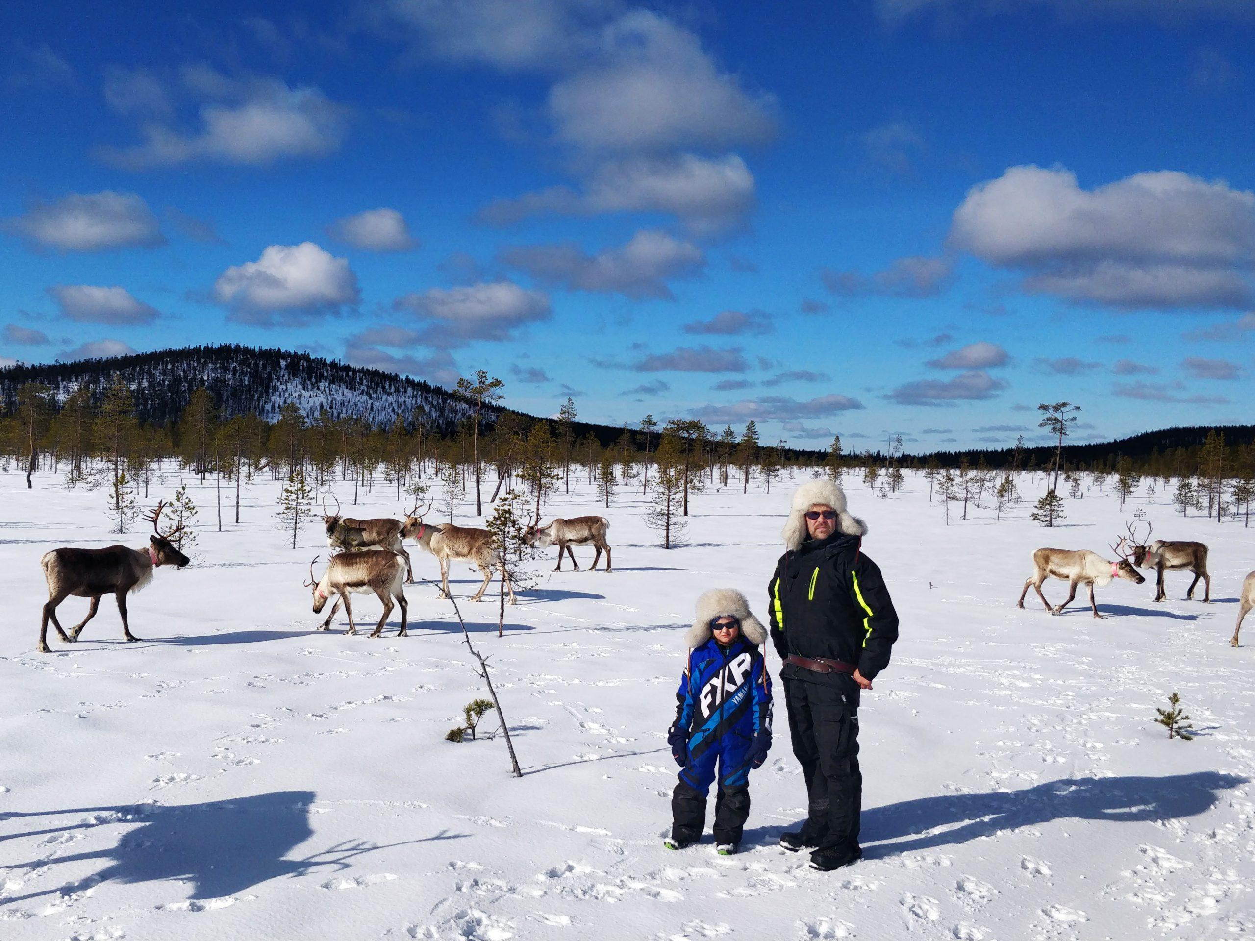 Pasi Oinas poikansa kanssa lumisella aavalla, ympärillä poroja.