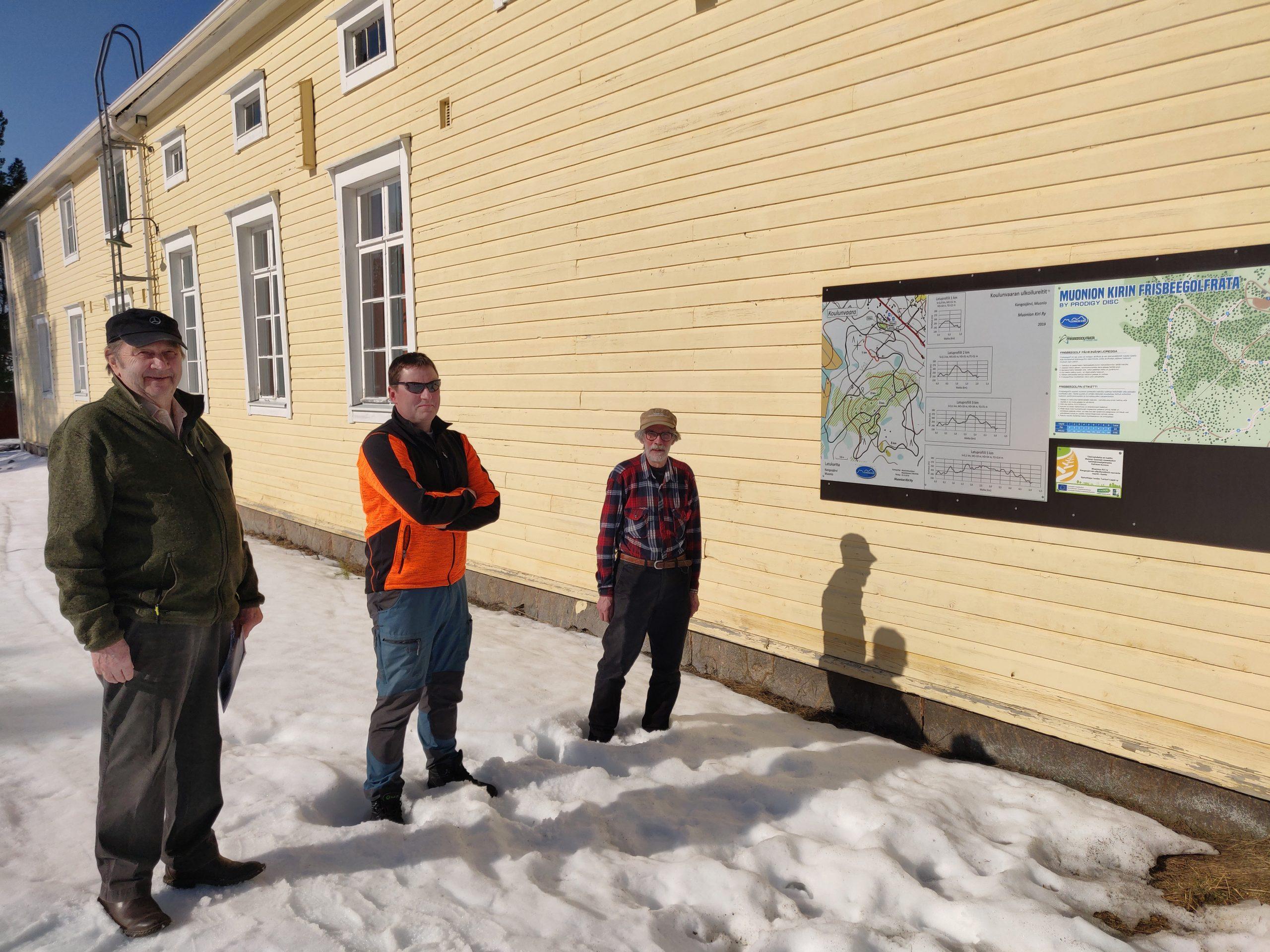 Kolme henkilöä kylätalon pihalla, taustalla frisbeegolf-radan kartta.