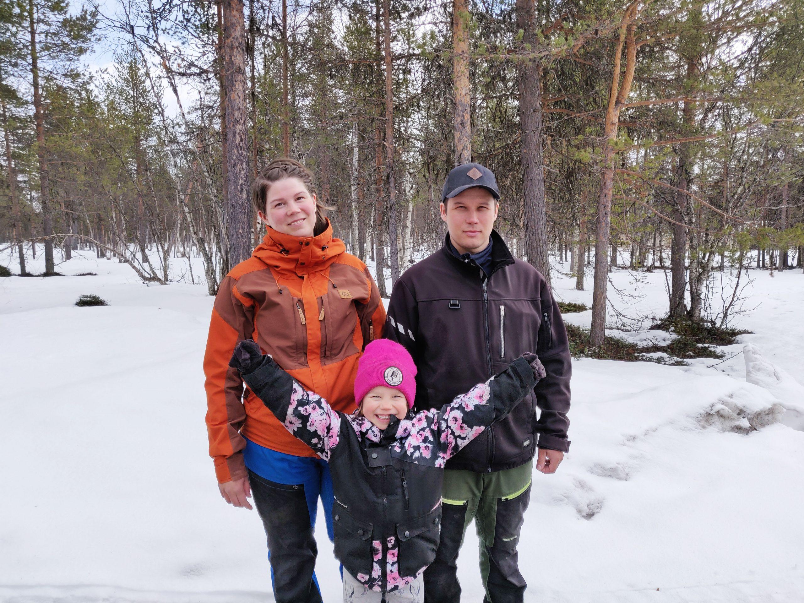Perhe poseeraa hymyillen kameralle lumisen metsän edessä.
