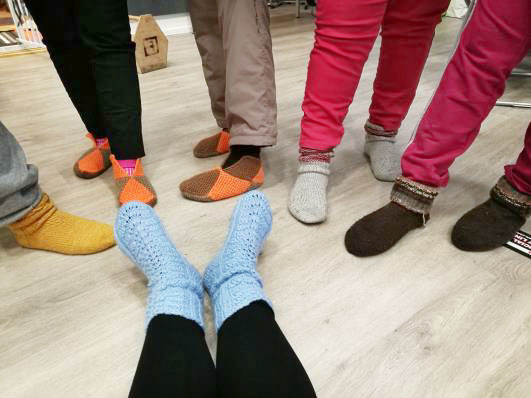 Ihmisten jalkoja, joissa on erivärisiä villasukkia.