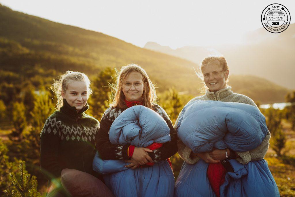 Kolme tyttöä istuu tunturissa makuupussit sylissään, nurkassa vesileima Tee se Suomessa Lappi.