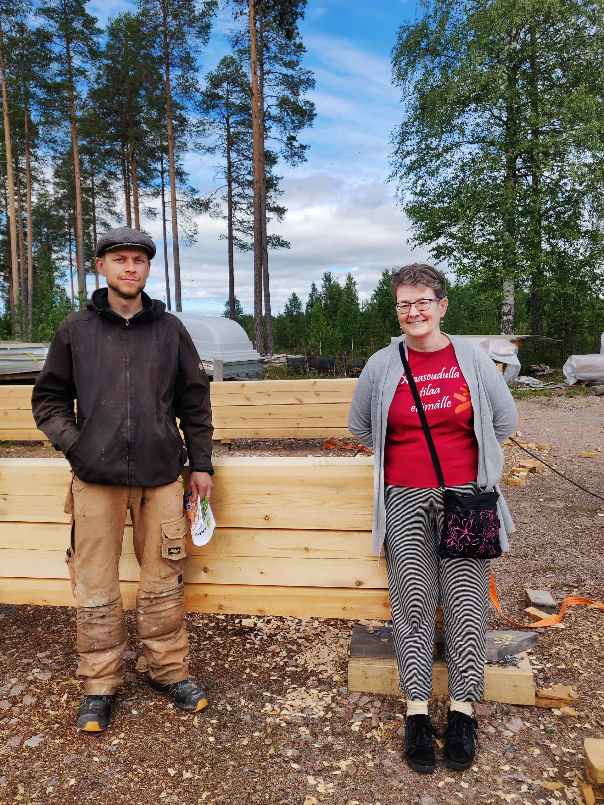 Jaakko Moilanen ja Anne Ristioja hymyilevät kameralle, taustalla hirsikehikko.