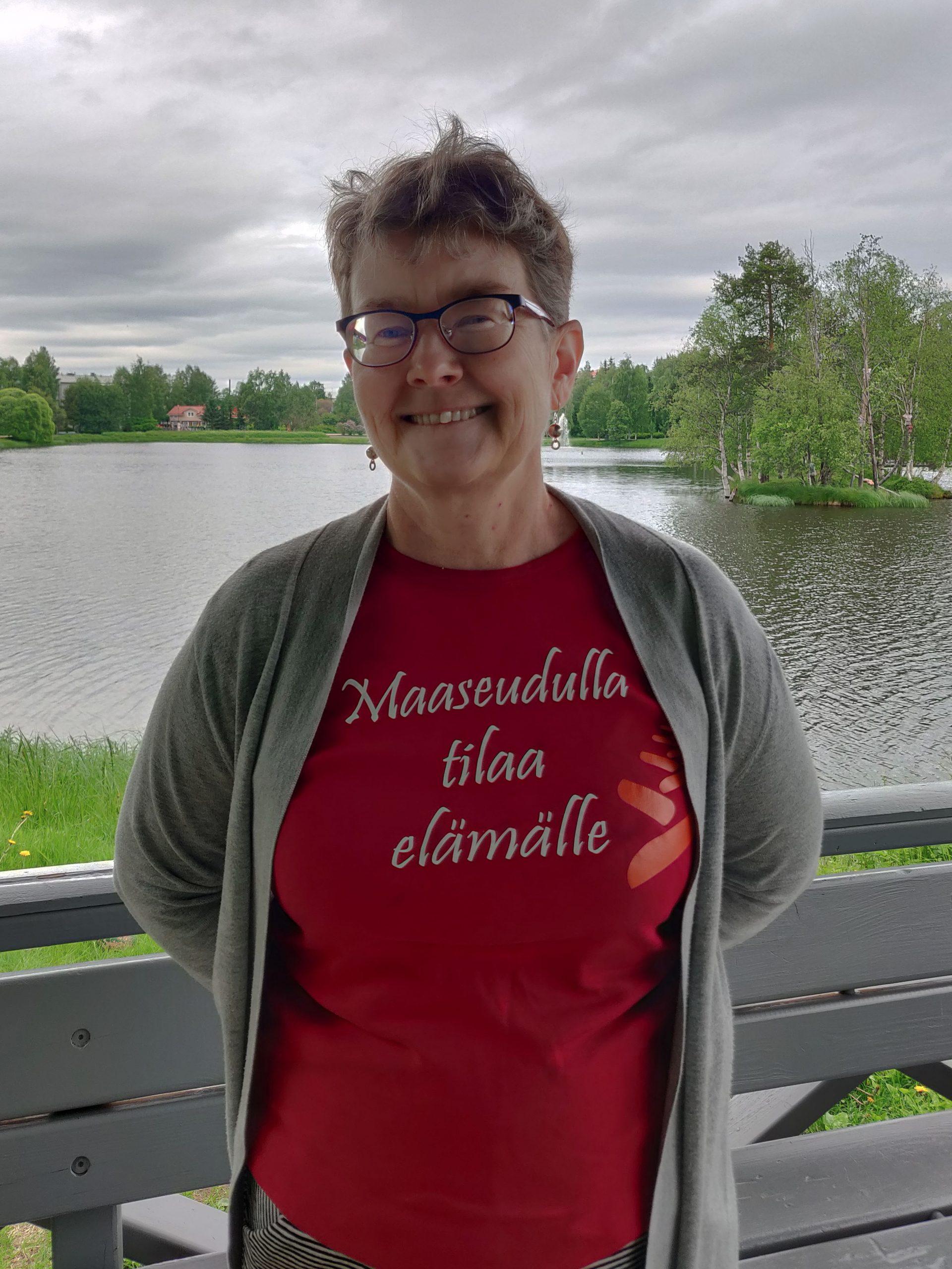 Anne Ristioja hymyilee kameralle, taustalla lampi, t-paidassa lukee maaseudulla tilaa elämälle.